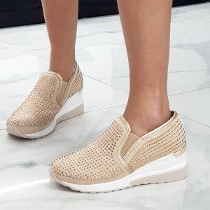 Sneaker zeppa intera. L'altezza del tacco è di cm 6. La composizione è di tessuto elasticizzato, con strass neri. Il colore è beige.